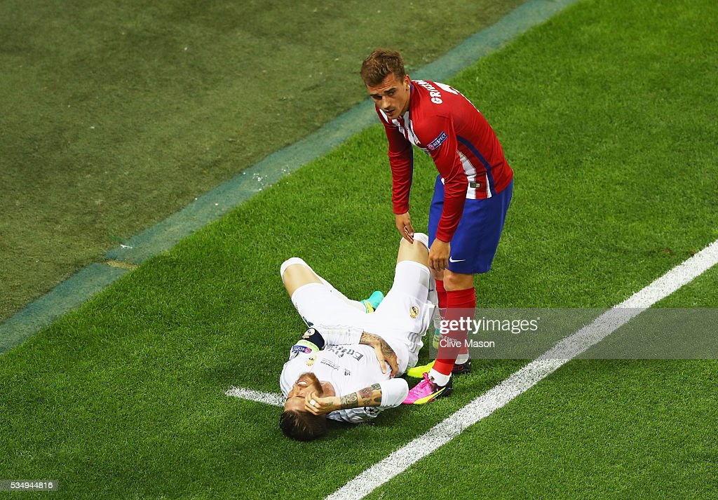 Sergio Ramos of Real Madrid is helped by <a gi-track='captionPersonalityLinkClicked' href=/galleries/search?phrase=Antoine+Griezmann&family=editorial&specificpeople=7197539 ng-click='$event.stopPropagation()'>Antoine Griezmann</a> of Atletico Madrid during the UEFA Champions League Final match between Real Madrid and Club Atletico de Madrid at Stadio Giuseppe Meazza on May 28, 2016 in Milan, Italy.