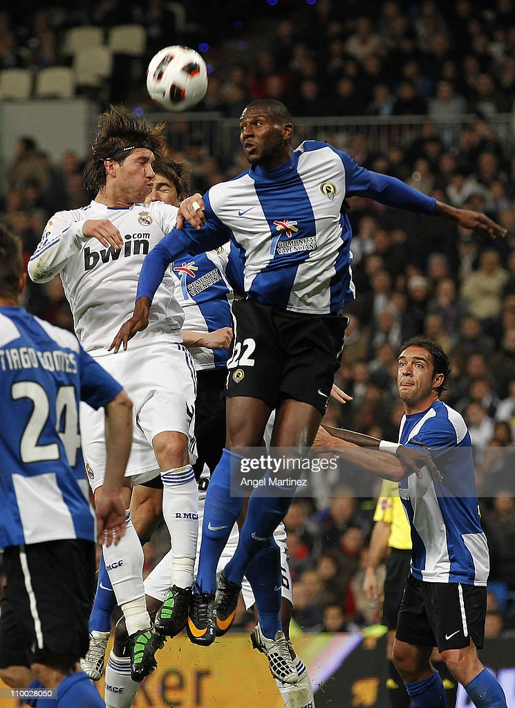 Sergio Ramos of Real Madrid jumps for a high ball with Olivier Thomert of Hercules during the La Liga match between Real Madrid and Hercules at Estadio Santiago Bernabeu on March 12, 2011 in Madrid, Spain.