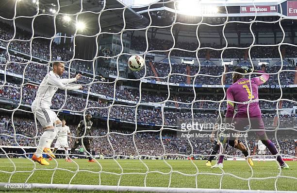 Sergio Ramos of Real Madrid scores the opening goal past Carlos Kameni of Malaga during the La Liga match between Real Madrid CF and Malaga at...