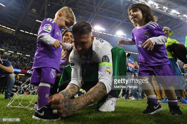 Sergio Ramos of Real Madrid ties his childs shoelace after the UEFA Champions League Final between Juventus and Real Madrid at National Stadium of...