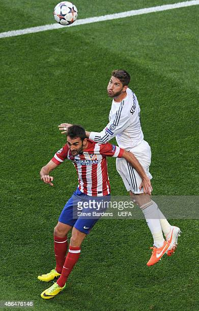 Sergio Ramos of Real Madrid wins a header with Adrian Lopez of Club Atletico de Madrid during the UEFA Champions League Final between Real Madrid CF...