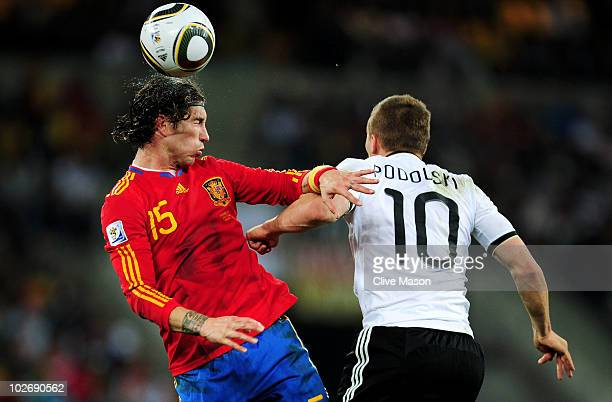 Sergio Ramos of Spain heads the ball under pressure from Lukas Podolski of Germany during the 2010 FIFA World Cup South Africa Semi Final match...