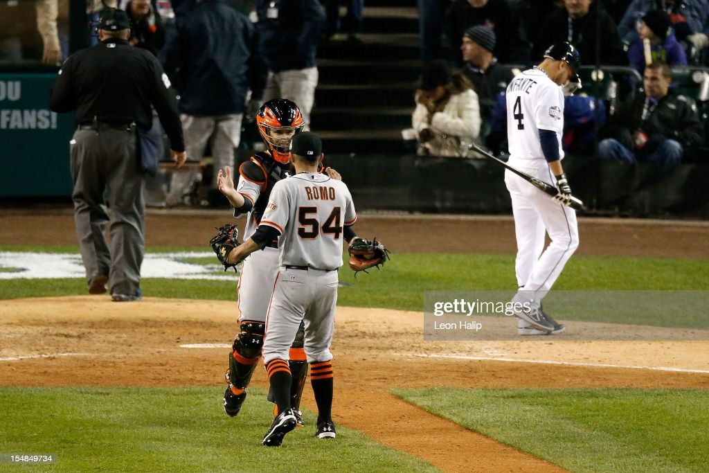 Sergio Romo of the San Francisco Giants celebrates with teammate Buster Posey after striking out Omar Infante of the Detroit Tigers to win Game Three...
