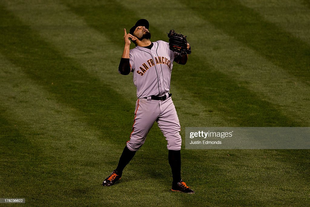 Sergio Romo #54 of the San Francisco Giants points to the sky to celebrate after he helped the Giants defeat the Colorado Rockies 5-3 at Coors Field on August 27, 2013 in Denver, Colorado.