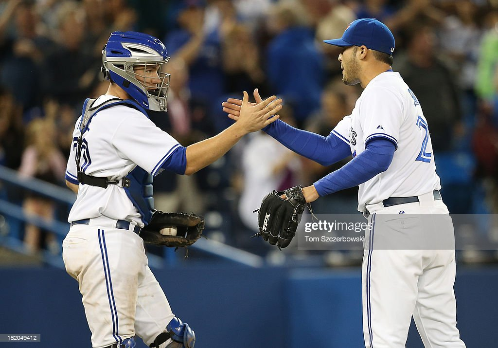 Sergio Santos #21 of the Toronto Blue Jays celebrates a victory with <a gi-track='captionPersonalityLinkClicked' href=/galleries/search?phrase=Josh+Thole&family=editorial&specificpeople=5741573 ng-click='$event.stopPropagation()'>Josh Thole</a> #30 after an MLB game against the Tampa Bay Rays on September 27, 2013 at Rogers Centre in Toronto, Ontario, Canada.