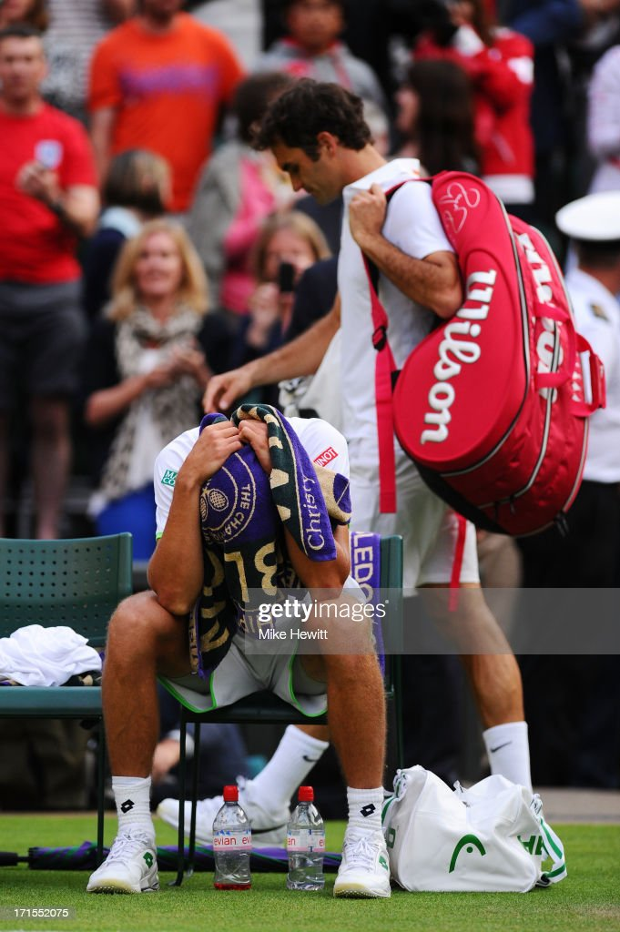 <a gi-track='captionPersonalityLinkClicked' href=/galleries/search?phrase=Sergiy+Stakhovsky&family=editorial&specificpeople=579263 ng-click='$event.stopPropagation()'>Sergiy Stakhovsky</a> of Ukraine reacts to his victory as <a gi-track='captionPersonalityLinkClicked' href=/galleries/search?phrase=Roger+Federer&family=editorial&specificpeople=157480 ng-click='$event.stopPropagation()'>Roger Federer</a> of Switzerland walks off court following their Gentlemen's Singles second round match on day three of the Wimbledon Lawn Tennis Championships at the All England Lawn Tennis and Croquet Club on June 26, 2013 in London, England.