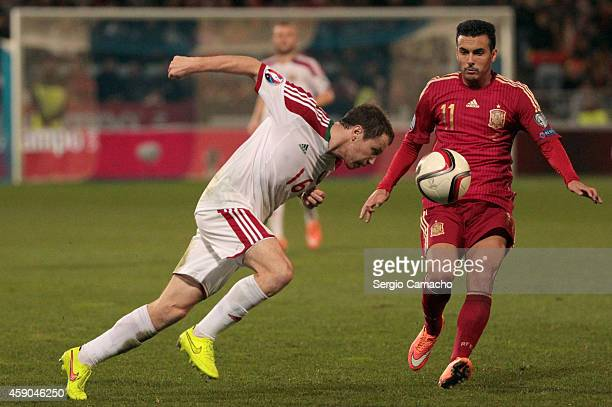Serguey Balanovich of Belarus controls the ball with the head against Pedro Rodriguez of Spain during the UEFA EURO 2016 Group C Qualifier football...