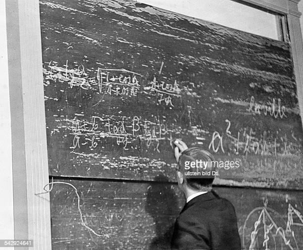 Schulen in NotLehrer schreibt an einer völlig abgenutzten Tafel in einer Berliner Volksschule Lehrmittel können wegen Geldmangels nicht ersetzt...