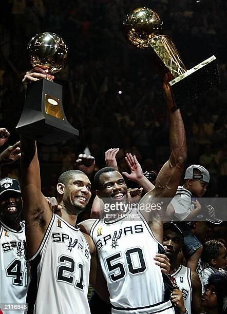 Series MVP Tim Duncan and David Robinson of the San Antonio Spurs holdup the MVP Trophy and the Larry O'Brian Championship trophy after beating the...