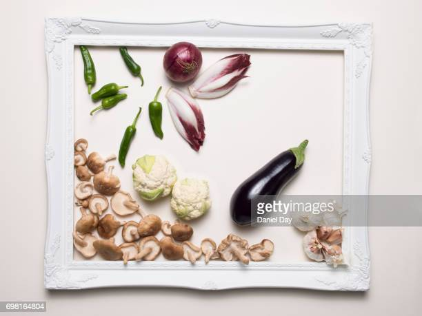 Series of images of different vegetables creatively laid out within a white picture frame on a white background