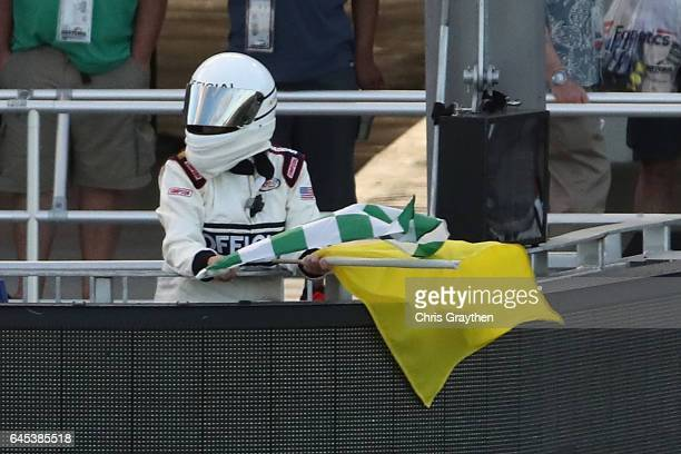 Series official waves a green and white checkered flag to end a segment during the NASCAR XFINITY Series PowerShares QQQ 300 at Daytona International...