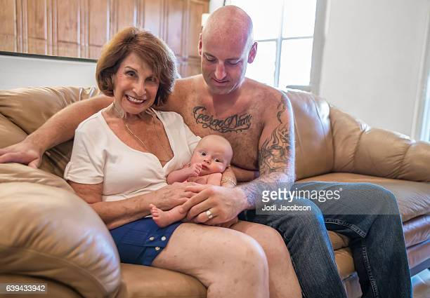 Series:Proud grandmother holds six week old grandson with tattooed father.