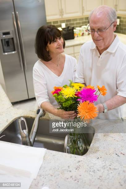 Series:Senior tender moment. Husband gives wife flowers at home