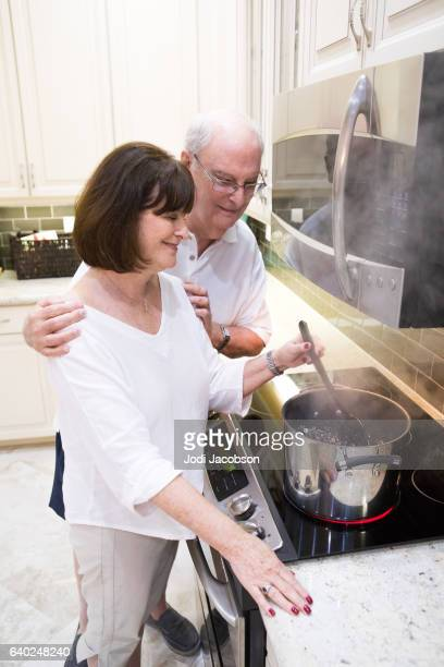 Series:Senior tender moment. Husband watches wife cooking at stove