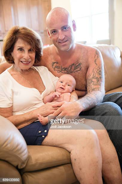 Series:Senior woman holds six week old grandson with tattooed father.