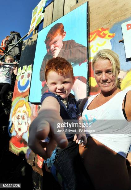 Serina and her son Michael Flynn residents of the Dale Farm travellers site stand in front of a photo of Michael outside the front gate to the camp...