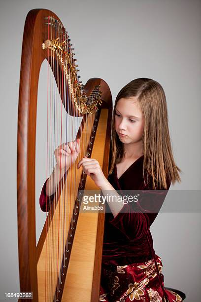 Serious 12-year old girl playing a harp