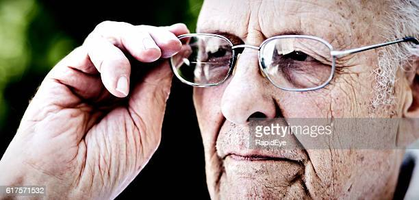 Serious 90 year old man looking through his spectacles