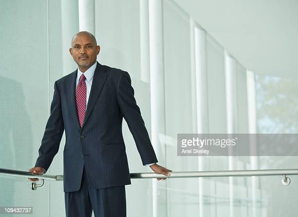 なアフリカ系アメリカ人のビジネスマン壁に手すり