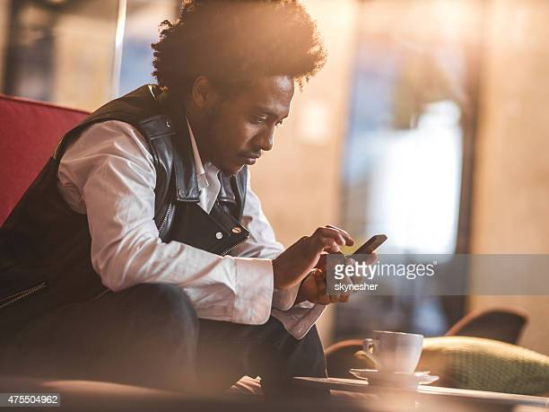 Serious African American man text messaging on cell phone.