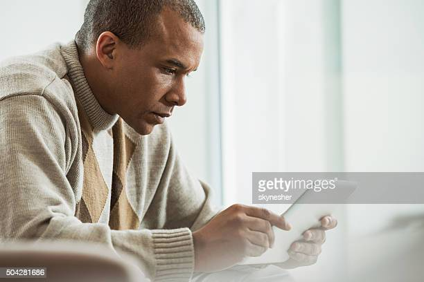 Serious African American using touchpad at home.