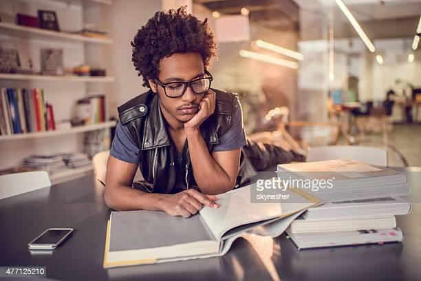 Ernst afrikanische amerikanische jungen Mannes studieren in der Bibliothek.