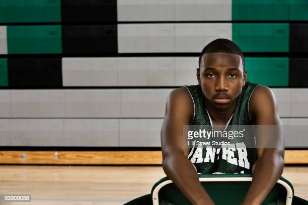 Serious African basketball player sitting on chair in gym