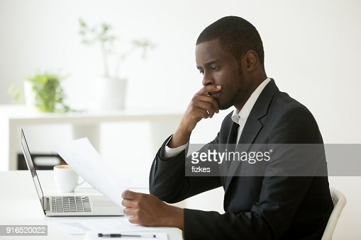Serious african-american businessman thinking of notice reading letter at workplace : Stock Photo