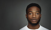 Portrait of serious millennial african-american man on black studio background, panorama with copy space