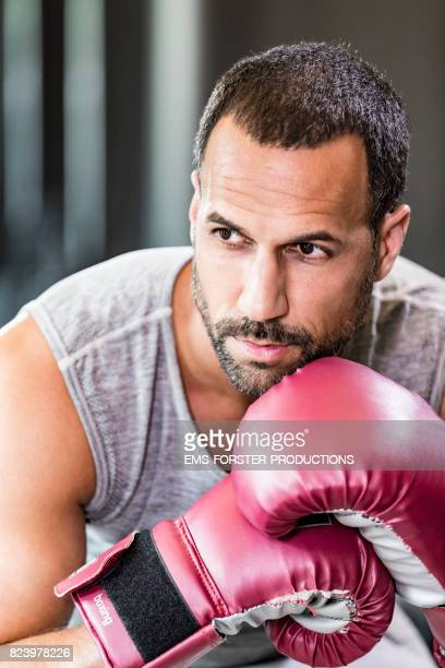 serious and concentratet fitness trainer is wearing boxing gloves