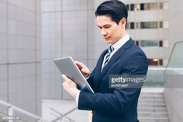 Serious asian businessman using digital tablet on street