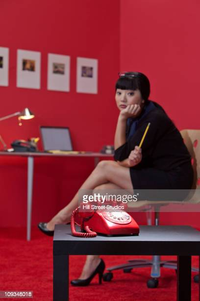 Serious Asian businesswoman waiting for the telephone to ring