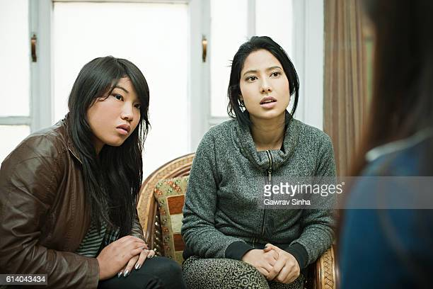 Serious Asian girls busy in conversation at living room.