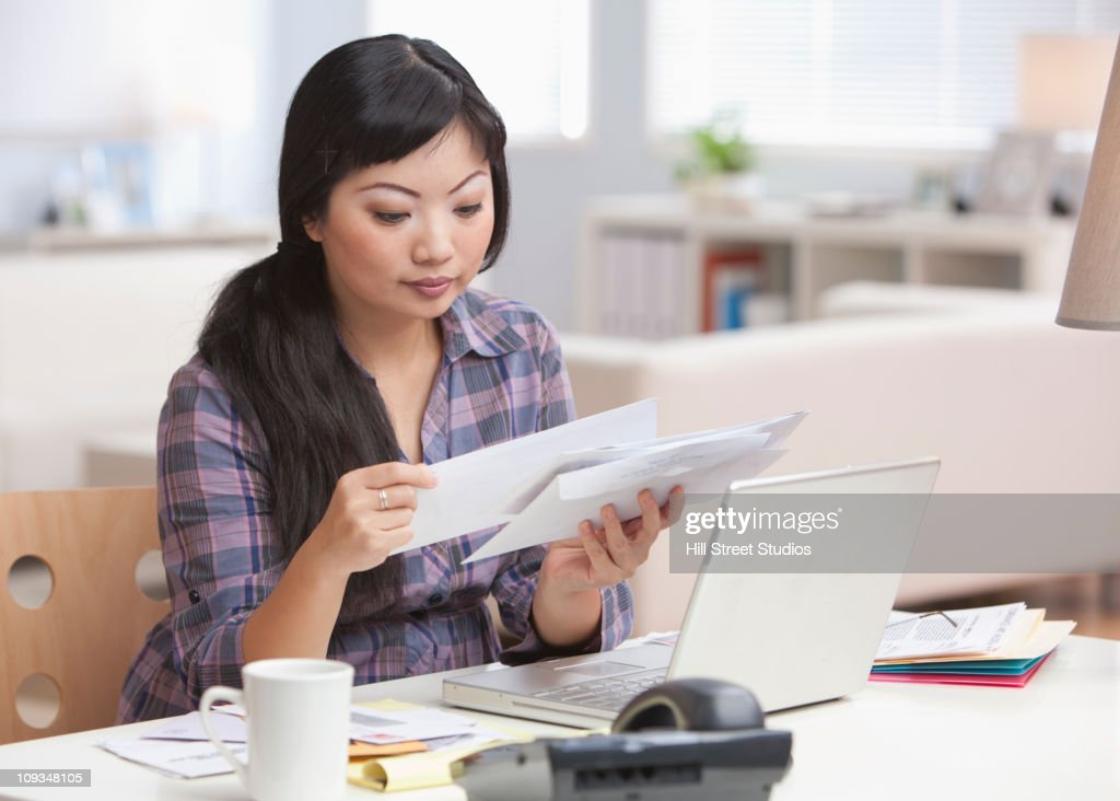 Serious Asian woman looking at mail in home office : Stock Photo