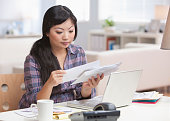 Serious Asian woman looking at mail in home office