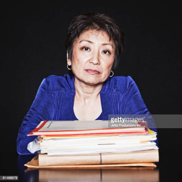 Serious Asian woman with stack of paperwork