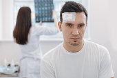 Brain concussion. Serious attractive young man standing in the hospital and looking at you while being wounded