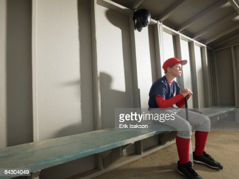Serious baseball player sitting in dugout