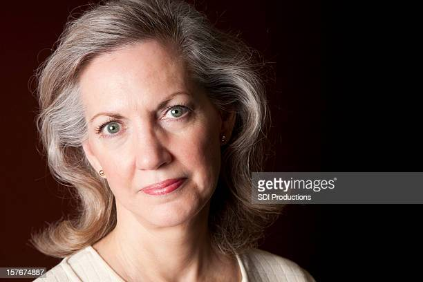 Serious Beautiful Mature Adult Woman Portrait on Dark Background