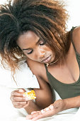 Serious black young woman holding a prescription sleeping pills bottle