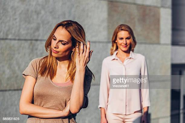 Serious blond woman outdoors with woman in background