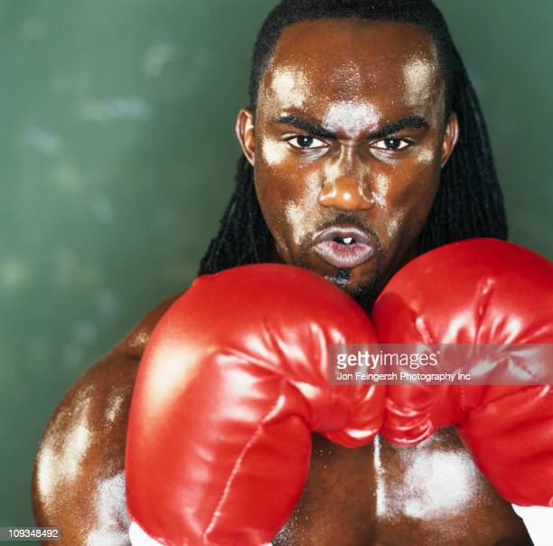 Serious boxer holding gloves up