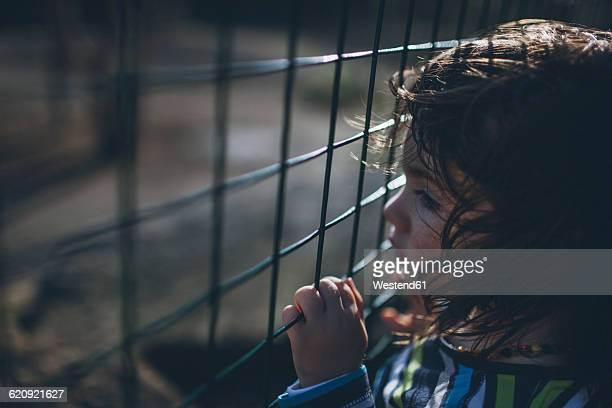Serious boy behind fence
