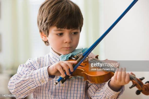 Serious boy playing violin