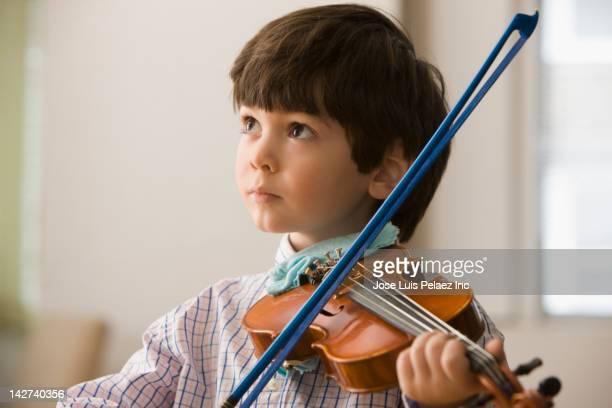 Serious boy playing violin