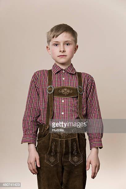 A serious boy wearing lederhosen