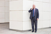 Portrait of serious senior handsome man looking at camera, talking on smartphone and standing at wall outdoors