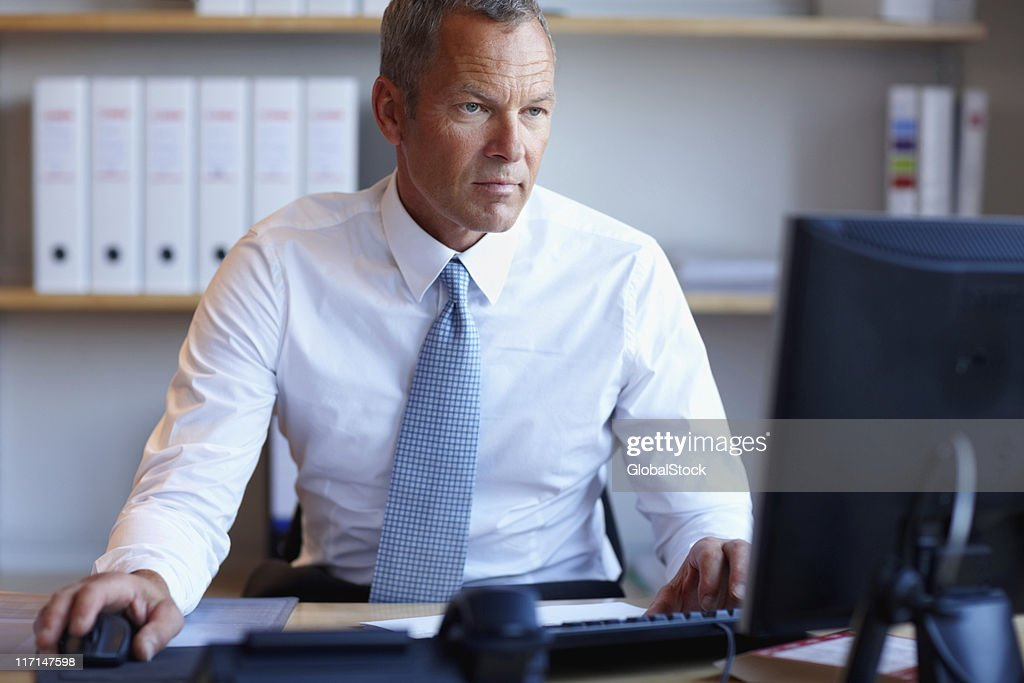 Serious business man working on a computer : Stock Photo