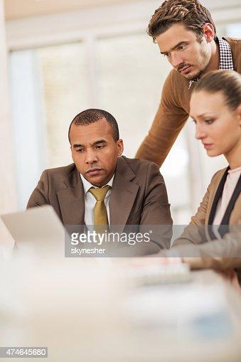 Gravi uomini d'affari utilizzando il computer portatile su una riunione.