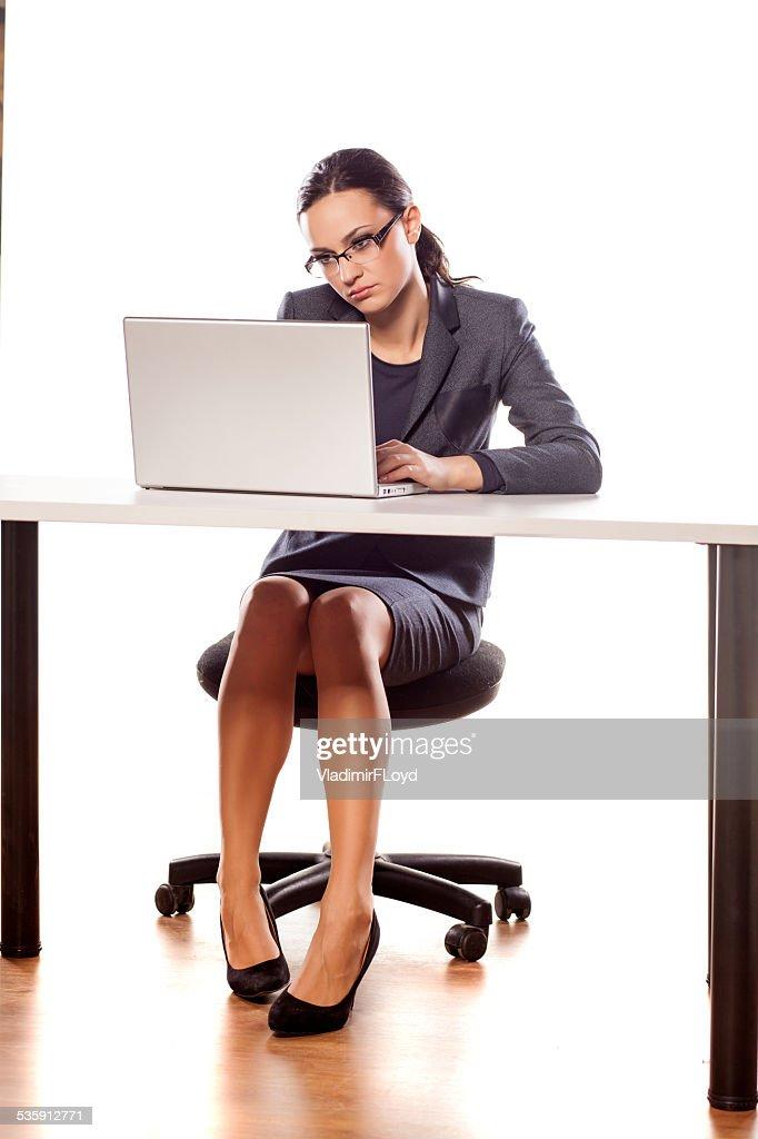 Graves mujer de negocios sentado en una mesa con capacidad para computadora portátil : Foto de stock